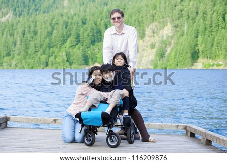 Disabled boy in wheelchair surrounded by family on lake pier - stock photo