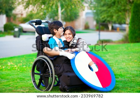 Disabled brother hugging older sister while sitting in wheelchair outdoors - stock photo