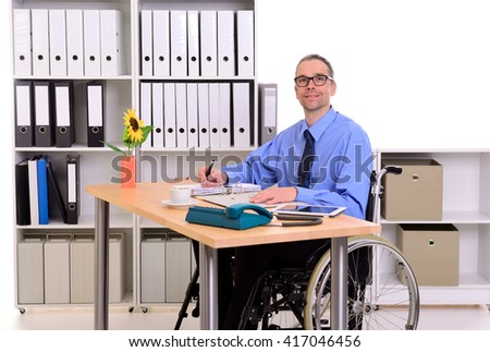 disabled business man in wheelchair is looking in to the camera - stock photo