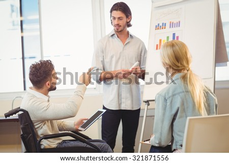 Disabled businessman pointing towards whiteboard while colleagues looking at it during meeting in creative office - stock photo