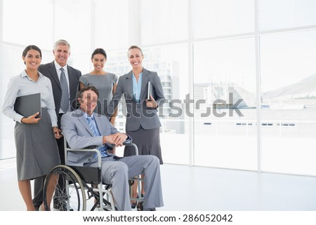 Disabled businessman with his colleagues smiling at camera in the office - stock photo