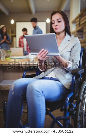 Disabled businesswoman using digital tablet in creative office