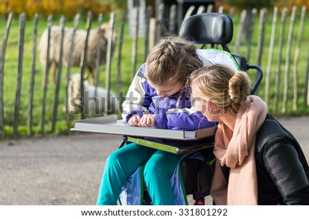 Disabled child in wheelchair relaxing outside together with a special needs care assistant / Working with disability - stock photo
