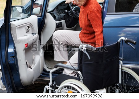 Disabled elder person driving car alone - stock photo