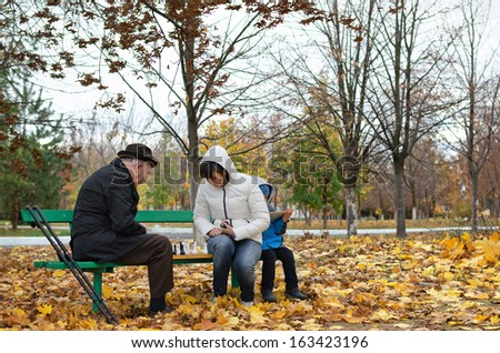 Disabled elderly man with crutches and an younger woman playing chess sitting together on a wooden park bench wrapped up warmly against cold autumn weather - stock photo