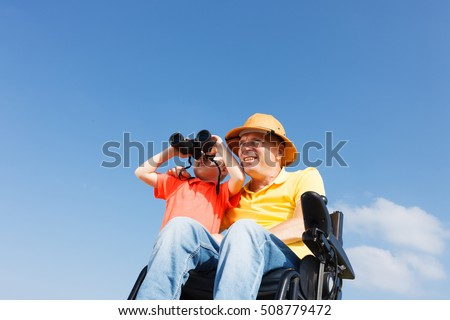 Disabled father and son play with binocular