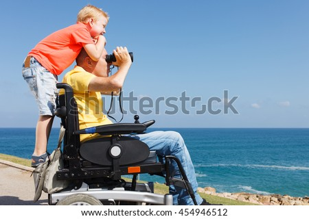 Disabled father looking through binoculars while his young boy