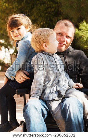 Disabled Father play with his little son and daughter - stock photo