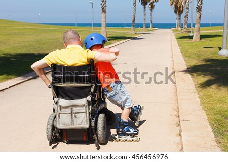 Disabled father rollerblading with son - stock photo