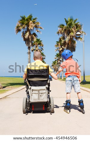 Disabled father with son - stock photo
