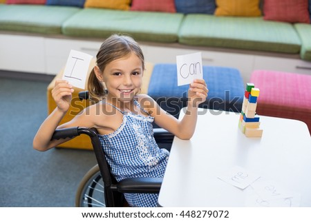 Disabled girl holding placard that reads I Can in library at school - stock photo