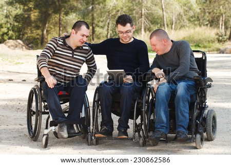 Disabled Happy friends  with digital Notebook - stock photo