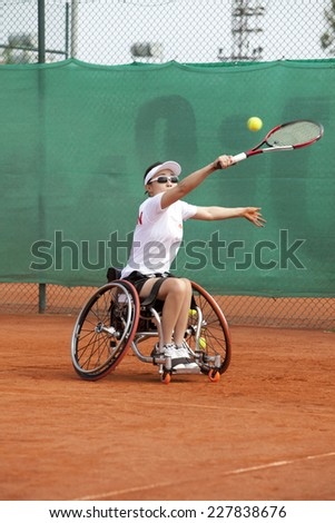 Disabled Japanese female tennis player. motion blur - stock photo