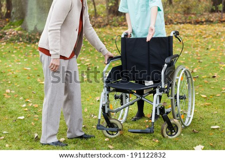 Disabled lady trying to sit on wheelchair in park - stock photo