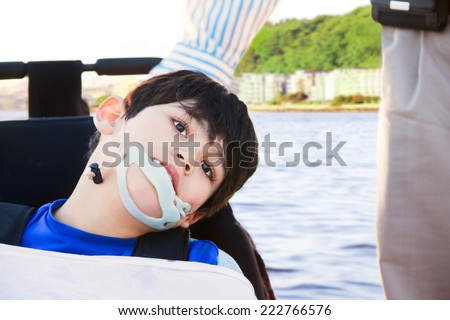 Disabled little boy in wheelchair next to father, outdoors - stock photo