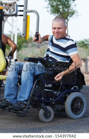 Disabled male in wheelchair working out with trainer. - stock photo