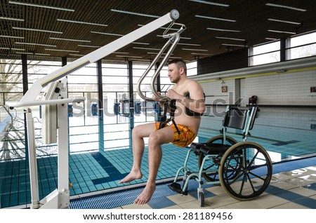 Disabled man in a swimming pool. Lift for the descent of people with disabilities into the pool. Wheelchair.