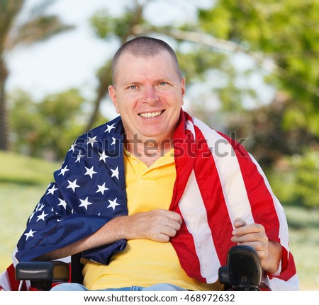 Disabled man sitting in wheelchair with flag of USA on the sholders