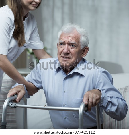 Disabled man using a walking frame with help of the nurse - stock photo