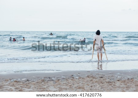 disabled man walking on the beach - stock photo