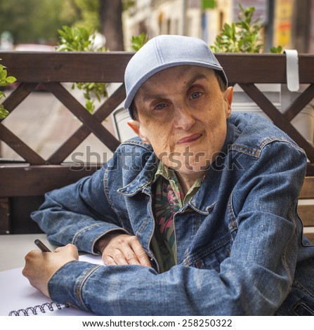 Disabled man with cerebral palsy sitting at outdoor cafe with a notebook and pencil. - stock photo