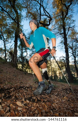 Disabled man with prosthetic leg, practicing Nordic Walking. - stock photo