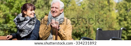 Disabled man with walking stick and wheelchair in park - stock photo