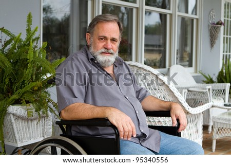 Disabled paraplegic man sits depressed in his wheelchair posing on the porch. - stock photo
