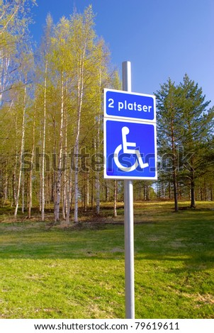 Disabled parking sign near green summer park