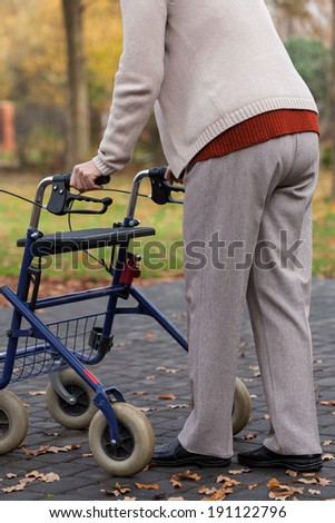 Disabled person with walker on the outside - stock photo
