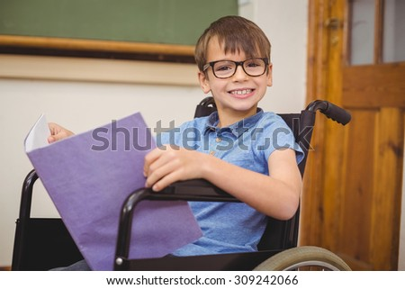 Disabled pupil smiling at camera at the elementary school - stock photo