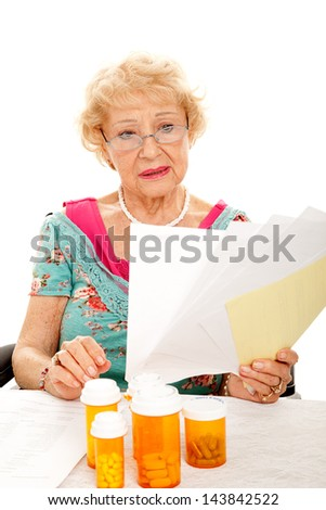 Disabled senior lady in wheelchair holding a pile of medical bills.  White background.