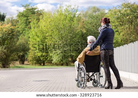 Disabled senior man and assistant in the park - stock photo