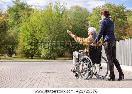 Disabled senior man and female caregiver outdoors - stock photo