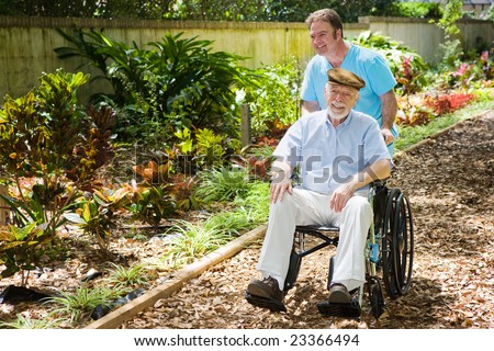Disabled senior man being pushed through a lovely garden by his nurse. - stock photo