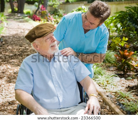 Disabled senior man in the garden with his male nurse. - stock photo