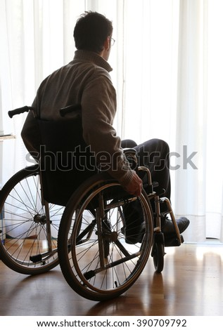 disabled sitting in a wheelchair in the room in front of the window