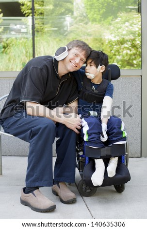 Disabled six year old boy in wheelchair hugging father while waiting at hospital - stock photo