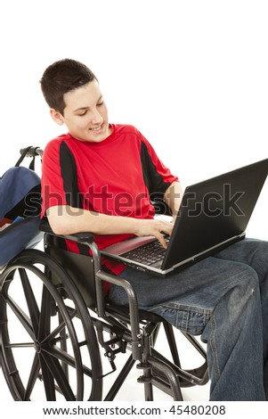 Disabled teen boy using a laptop in his wheelchair.  Isolated on white. - stock photo