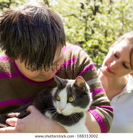 disabled woman cuddles a cute cat - stock photo