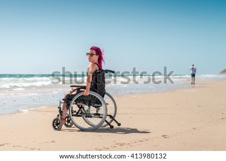 Disabled woman enjoys the beach and sun while the man was running by - stock photo