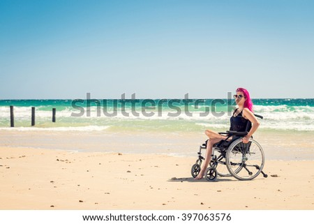 Disabled woman in the wheelchair at the beach. Cross-processed and color-toned image