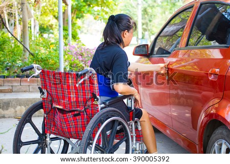Disabled woman on wheelchair opening a car door - stock photo