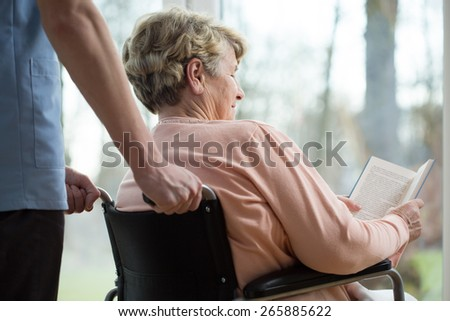 Disabled woman reading book in retirement home - stock photo