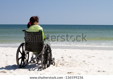 Disabled woman sits alone in a wheelchair on a sandy beach watching the ocean waves.