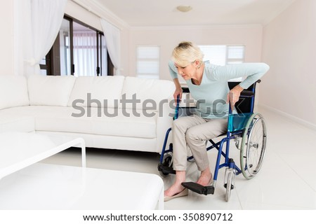 disabled woman trying to get up from wheelchair in living room - stock photo