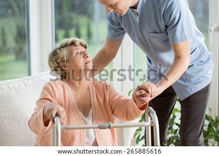 Disabled woman using walker assisted by physiotherapist - stock photo