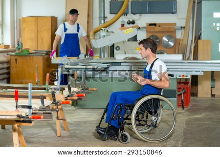 disabled worker in wheelchair in a carpenter's workshop - stock photo