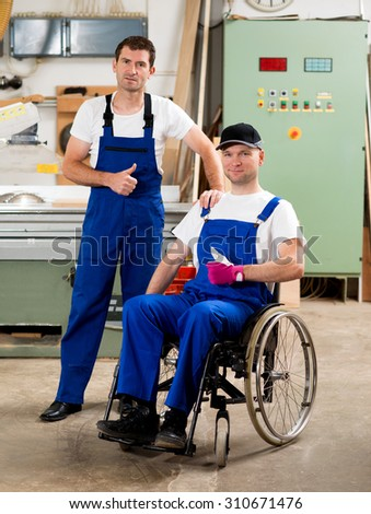disabled worker in wheelchair in a carpenter's workshop with his colleague with thumb up - stock photo