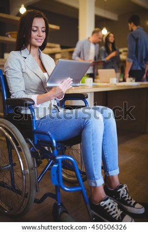 Disabled young businesswoman smiling while using digital tablet in creative office - stock photo